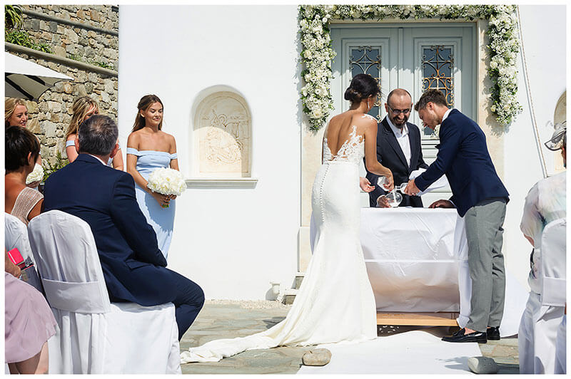 Bride groom doing salt ceremony watched by guests at Royal Myconian Resort Mykonos