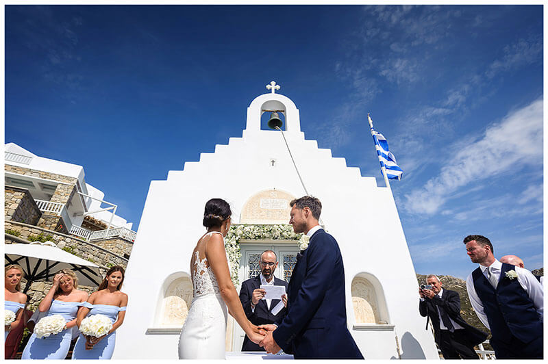 Bride groom holding hands in front of white chapel at Royal Myconian Resort as officiant reads from sheet of paper watched by videographer, usher and bridesmaids