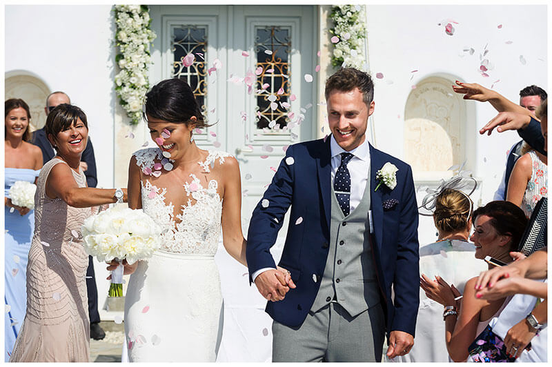 Smiling bride groom walk down aisle as guests throw confetti at Royal Myconian Resort Mykonos white chapel wedding