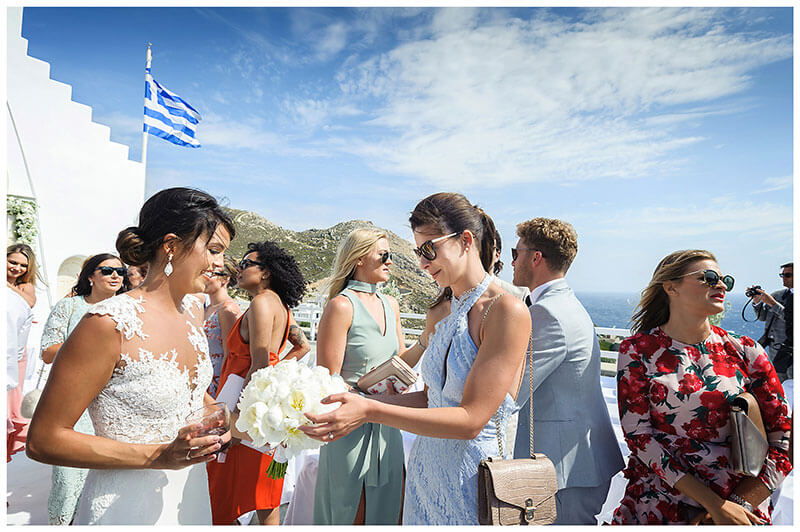 Bride shows female guest in blue dress her white bouquet at Royal Myconian Resort Mykonos wedding