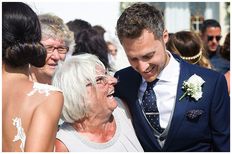 smiling Groom hugs smiling Grandmother