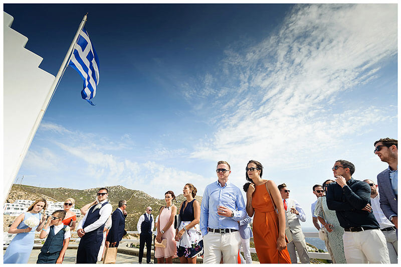 Wedding guests under a greek blue sky and greek flag