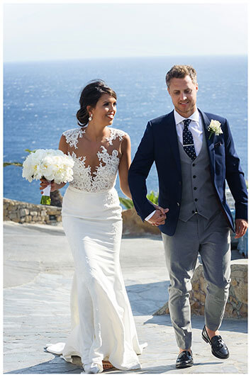 smiling bride looks at her groom as they walk up hill with sea behind them at Royal Myconian Resort Mykonos wedding