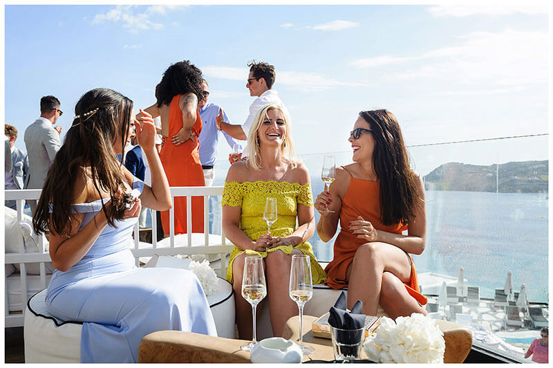 three female guetss laughing and enjoying a glass of Champagne while sitting on white seats at Royal Myconian Resort wedding