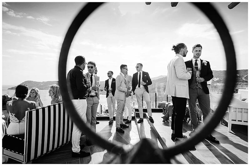 Guys viewed through metal hoop during drinks reception at Royal Myconian Resort wedding