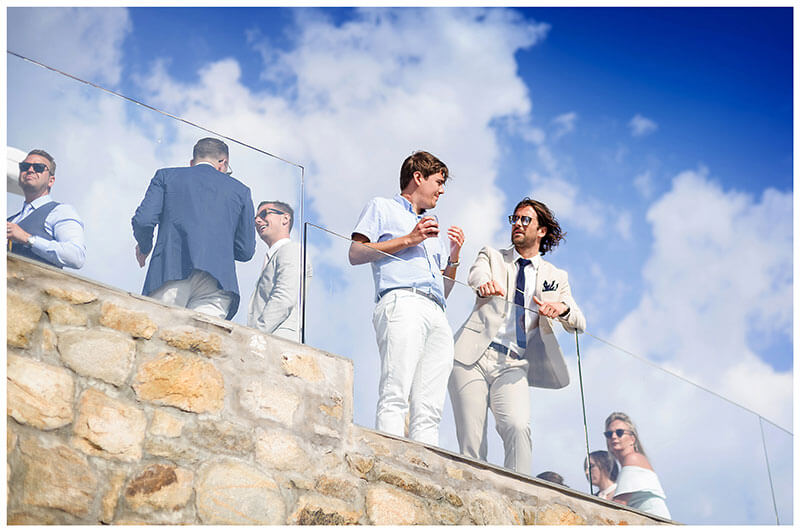 Guys in conversation viewed against a blue sky at Royal Myconian Resort wedding
