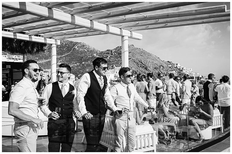 Four guys looking out to sea from Royal Myconian Resort balcony during wedding reception