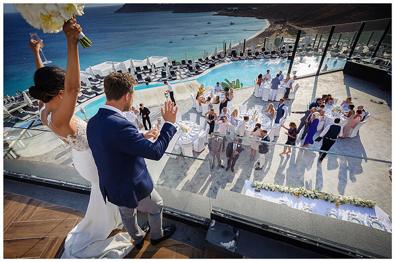 Groom wave at guests below as bride raises glass and bouquet in truimp during Royal Myconian Resort wedding