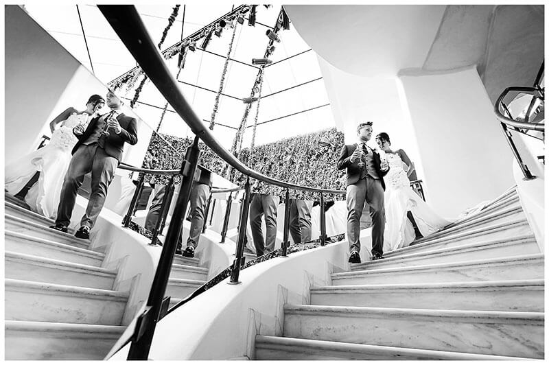 Bride groom walking down stairs reflected in mirrors during Royal Myconian Resort wedding reception