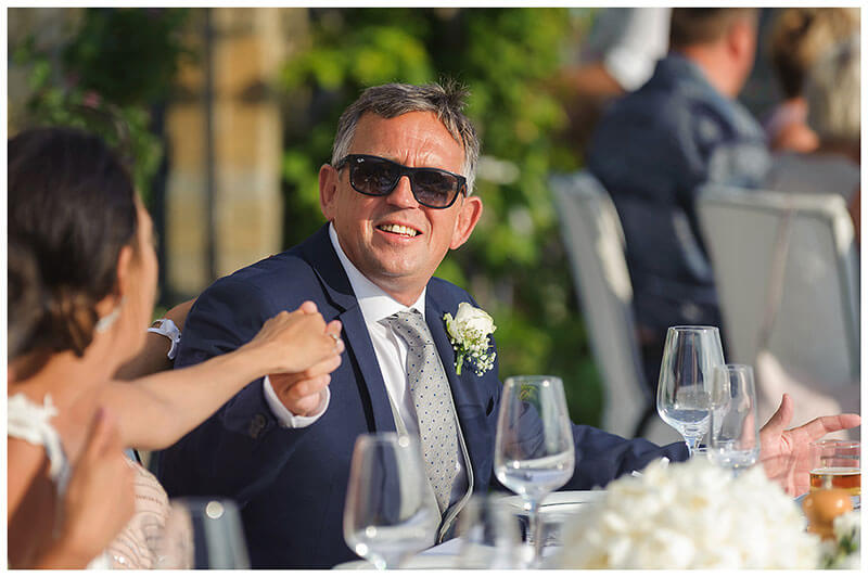 father of the bride, weraring sunglasses, takes Brides hand whilst sat at dining table at Royal Myconian Resort wedding reception