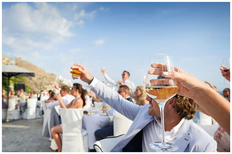 All the wedding guests raise a glass to the happy couple during Royal Myconian Resort wedding
