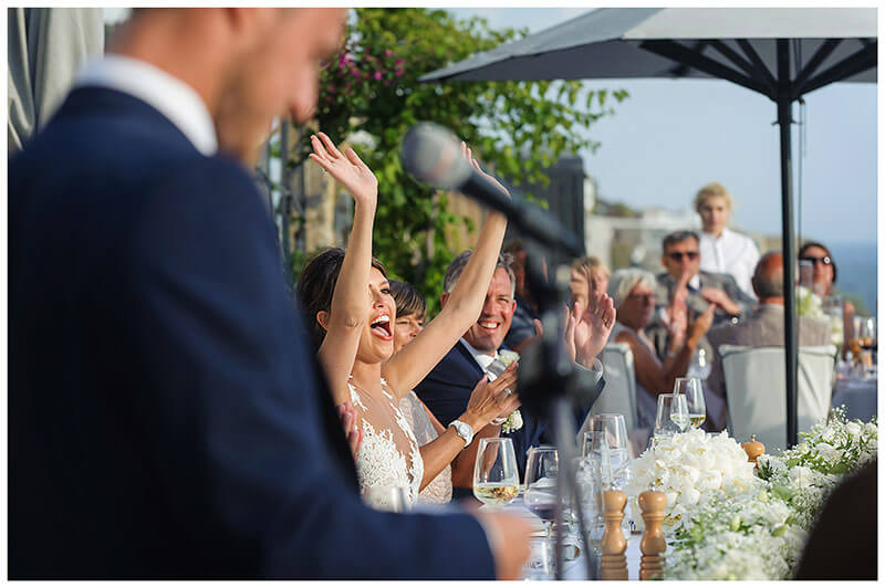 Bride raises arms in celebration during grooms speech at Royal Myconian Resort wedding reception