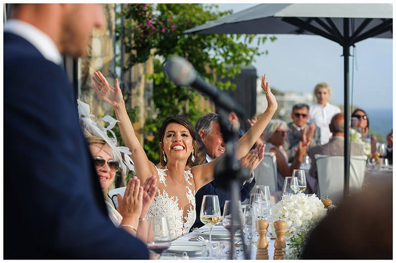 Big smiling bride celebrates grooms speech by raising arms in his direction at Royal Myconian Resort wedding reception