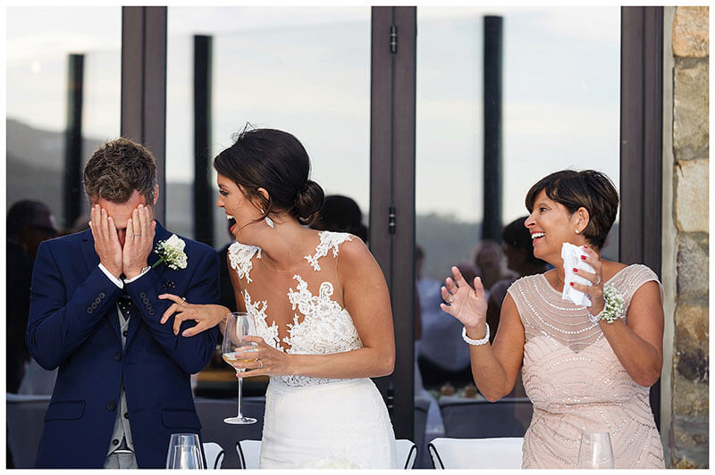 Groom burries head in hands as bride laughs during speeches at Royal Myconian Resort wedding reception