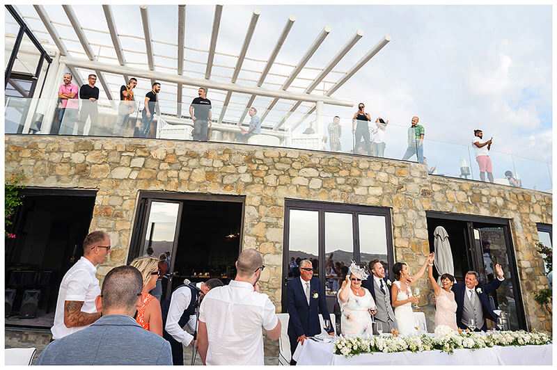 Onlookers look down from balcony to watch speeches of Royal Myconian Resort wedding reception