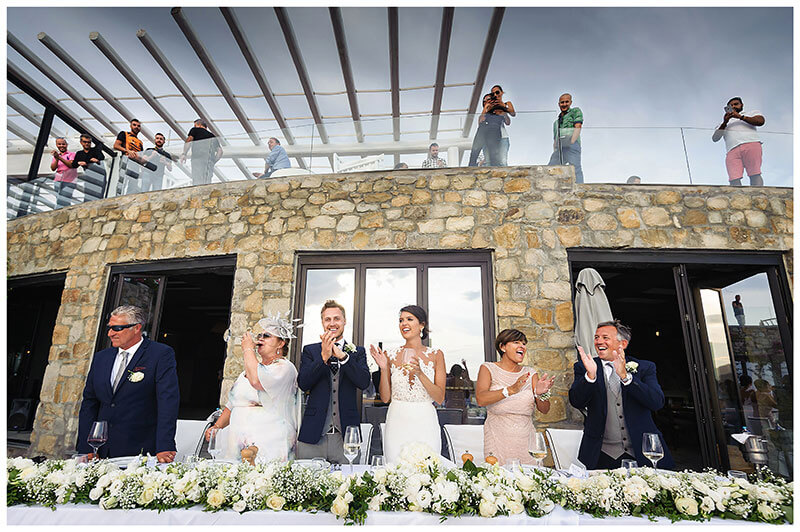bride groom appluad guests during Royal Myconian Resort wedding reception on lookers on balcony above watching
