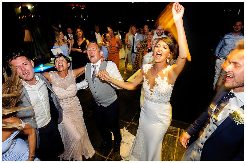 Bride groom guests singing and dancing during evening at Royal Myconian Resort wedding reception
