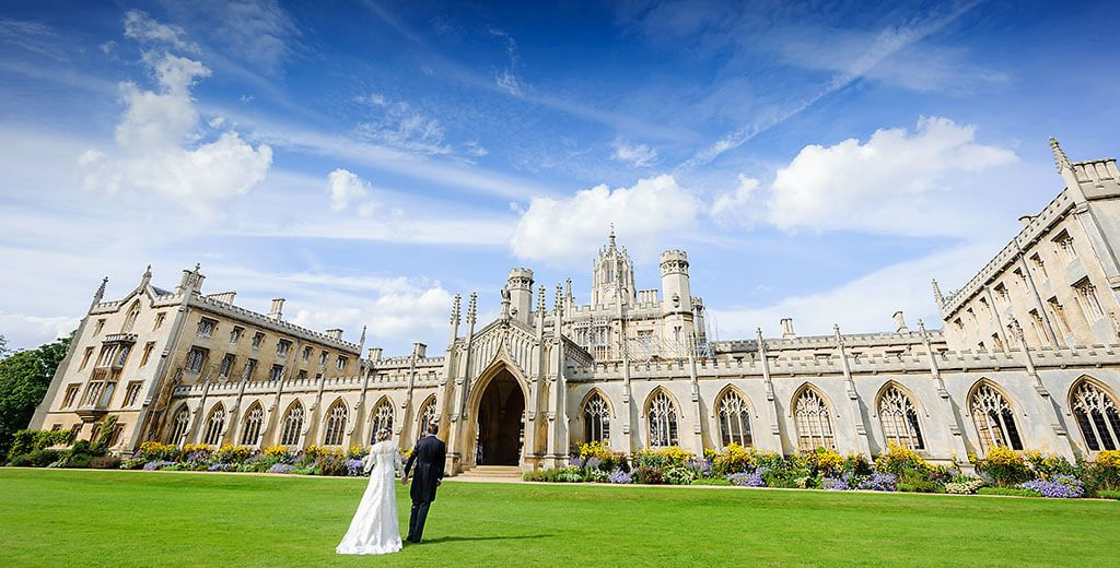 St Johns college Cambridge wedding photographer bride groom hold hands as they walk across the grass towards the collge