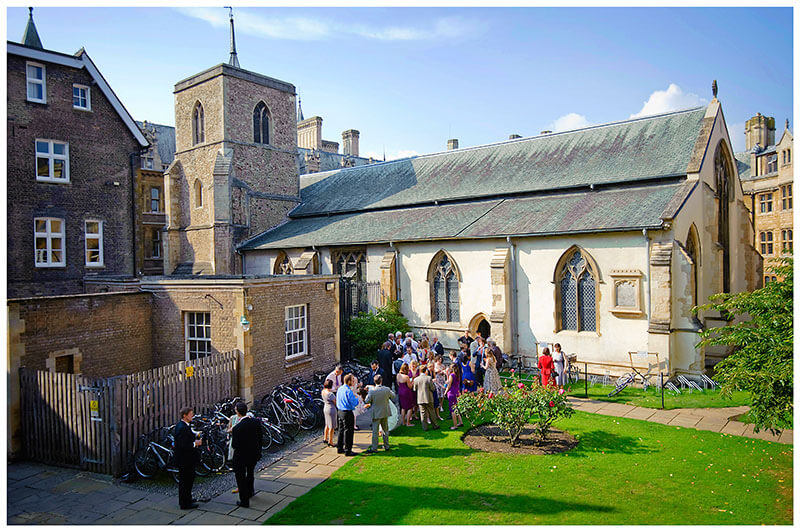 Cambridge wedding venue Michaelhouse guests in back courtyard enjoying sunshine