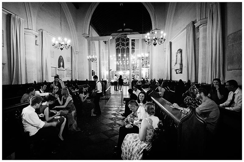 Cambridge wedding venue Michaelhouse guests sat in pews talking