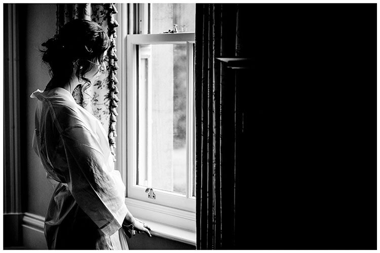 Bridesmaid looking thoughtfully out of window during preparations