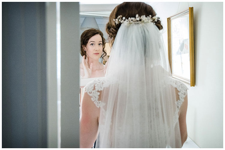 Looking at Bride over her shoulder as she checks her hair in a mirror before departing for the ceremony. Favourite wedding photography 2018