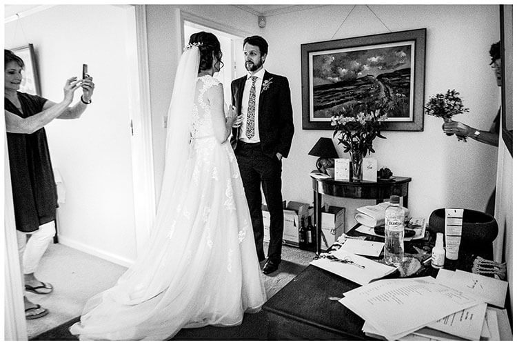 Bride talks to brother in hallway as make up artist takes photo of the back of the brides veil in hair whilst brides mum enters holding bouquet. favourite wedding photography of 2018