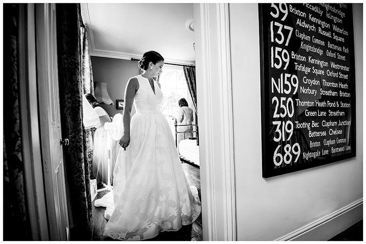 Bride framed in door way of bedroom about to leave bus route sign on wall favourite wedding photography 2018