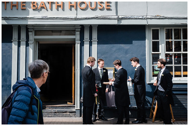 Groom and ushers outside pub The Bath House in Cambridge sorting last minute items before heading to Kings College for Ceremony passer by looks at them