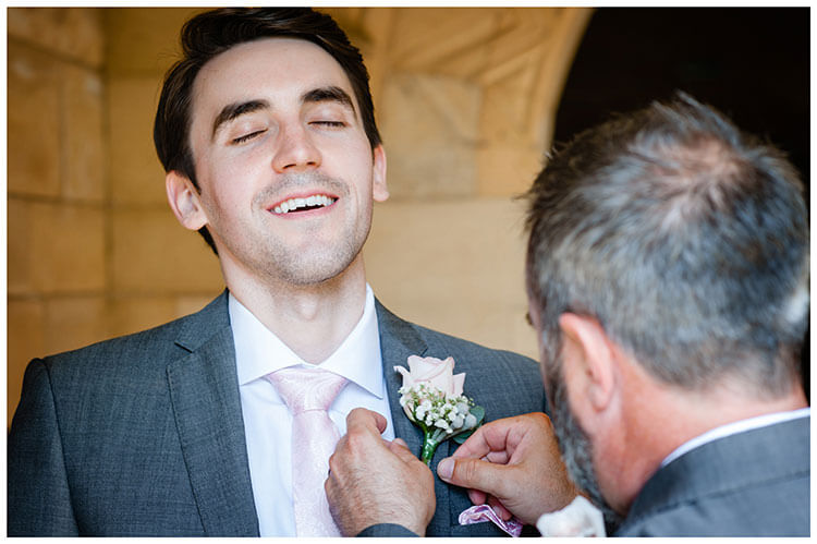 Groom lets out a nervous sigh as his button hole is fixed