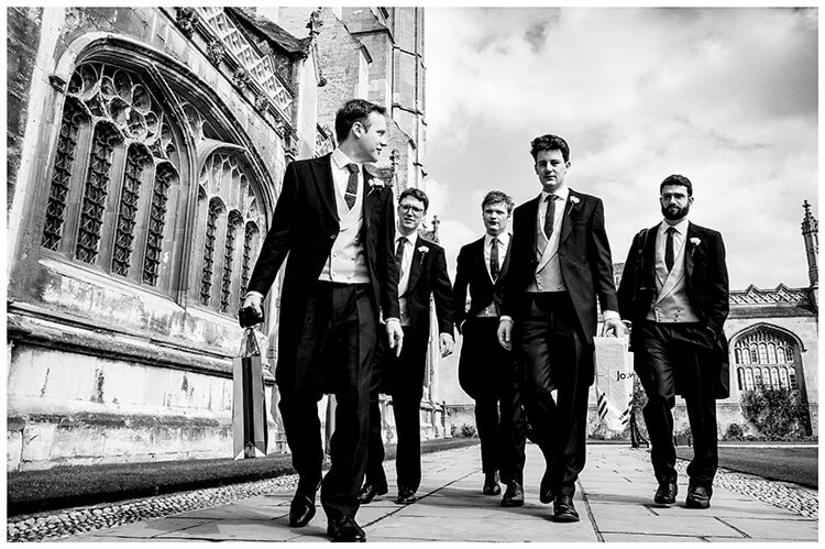 groom and groomsmen walking towards Kings College Chapel for the ceremony