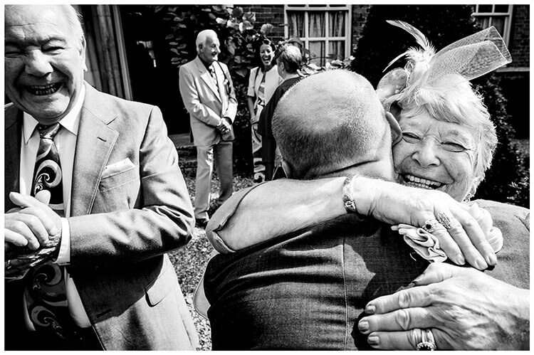 Elderly lady smiles broardly as she gives a big hug to male guest smiling gent watches