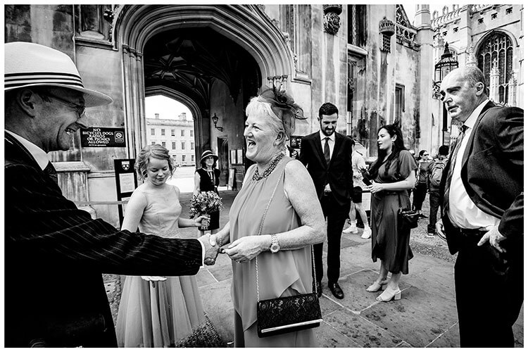 Guests greet each other outside Kings College Cambridge prior to wedding ceremony