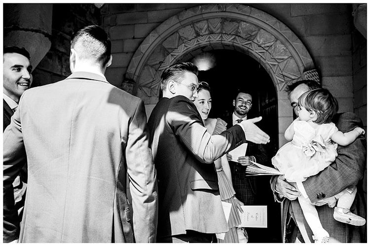 Man offers hand shake to young flower girl in arms of her father in enterance to St Peters church, Edensor before wedding ceremony starts Favourite wedding photography