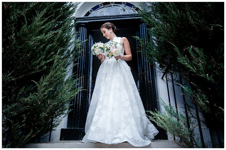 Bride standing on steps outside house holding two bouquets favourite wedding photography 2018