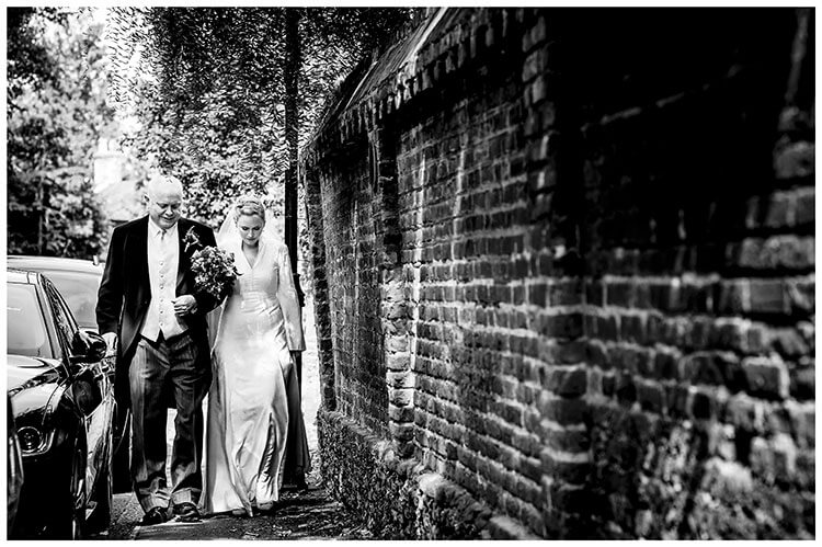 Bride walking arm in arm along path between parked cars and brick wall towards the ceremony