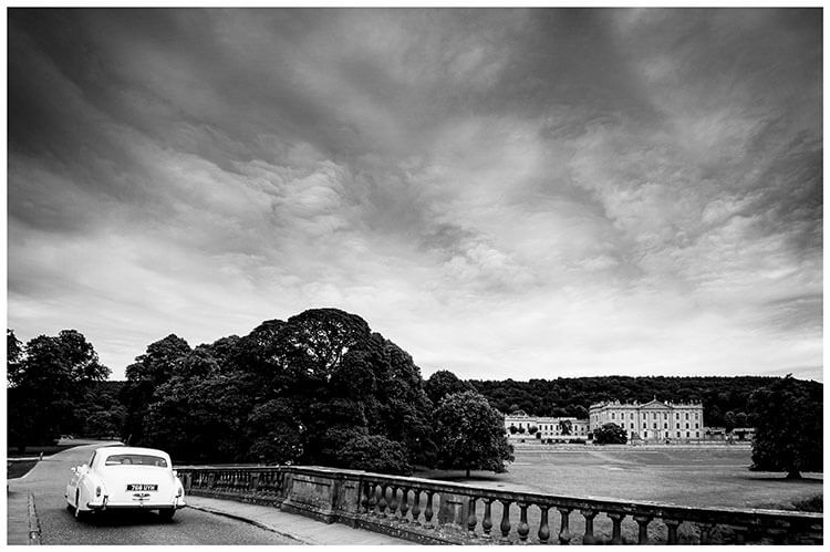 White Wedding car drives over bridge with chatsworth House in Background