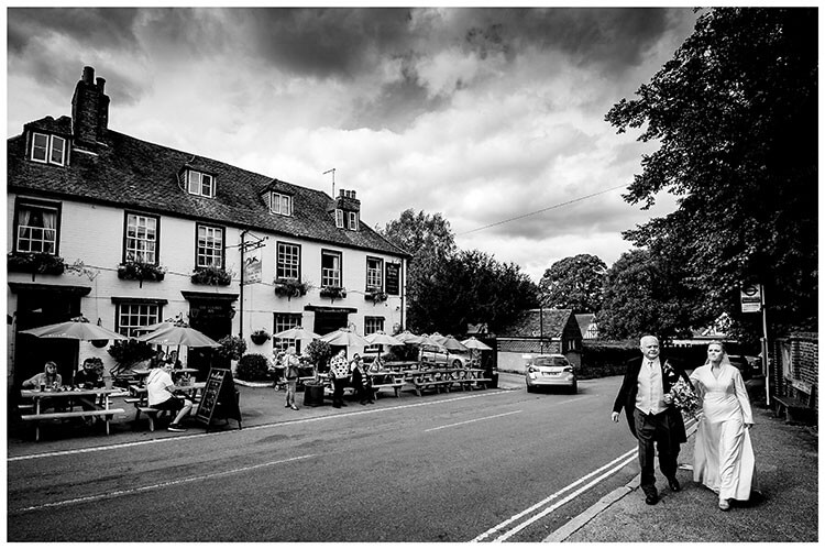 Bride and her father walking to the church with people in the pub garden looking on