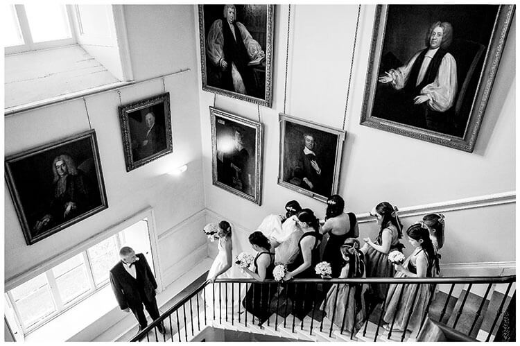 Father of Bride waits on stairs for the Bridal party to catch up, grand portraits on walls
