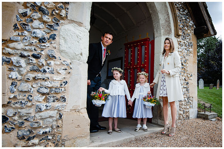 flower girls with their mother and father waiting in enterance of church for bride to arrive