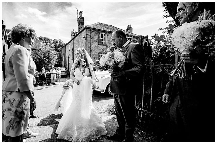 Smiling bride met by parents at St Peters church, Edensor gate