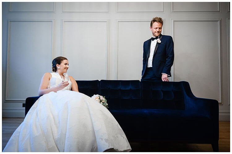 Bride sat on blue sofa groom standing behind at Old Marylebone Town Hall wedding