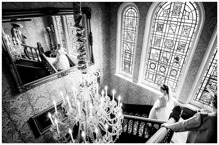 Bride followed down grand staircase by mother reflected in large wall mirror at Kilworth House wedding