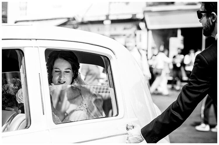 Bride sat in car as door is about to be opened Kings College Cambridge wedding