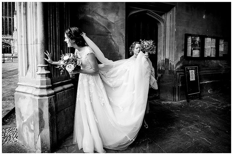Bride checking all guests have arrived for wedding ceremony at Kings College Cambridge as Bridesmaid lifts back of brides dress