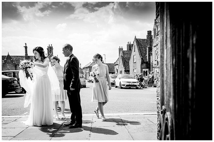 Bride adjusts viel at enterance to Ramsey Cambrideshire church watched by Father and Bridesmaids