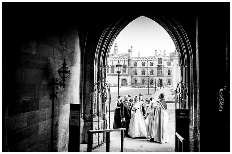 Bridal party at entrance to chapel at Kings College Cambridge viewed from inside chapel