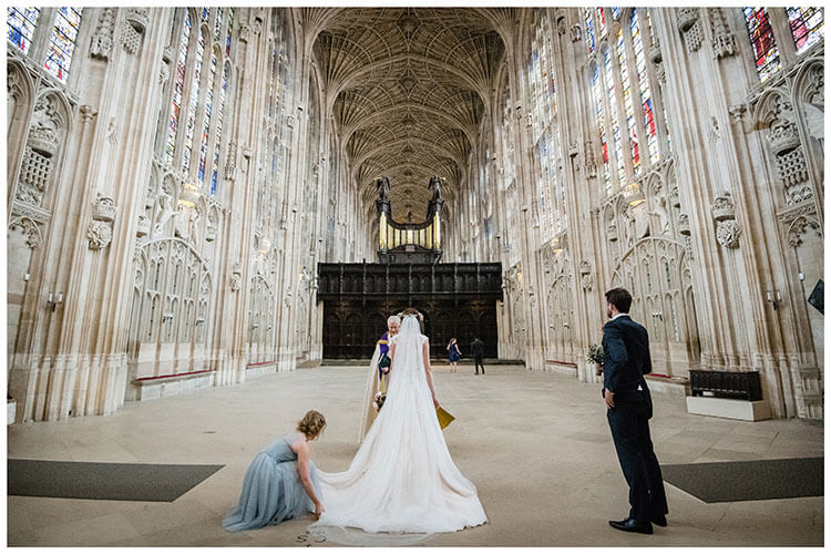 Wedding guests arrive late as bride has her wedding dress adjusted before walking up the aisle at Kings college Cambridge Chapel favourite wedding photography 2018