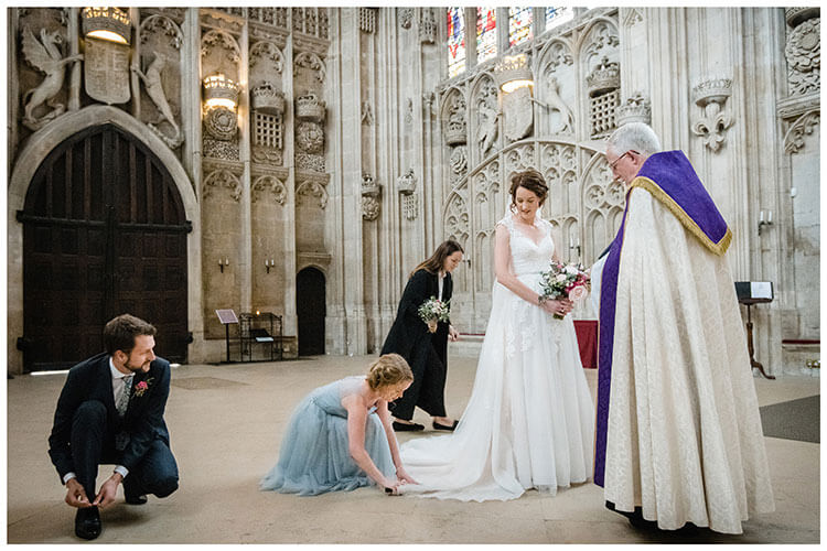 Bride looks down at Bridesmaid as she adjusts brides dress, escort ties shoe lace vicar standing in front of bride, church assistant holding bridesmaids bouquet in background at Kings College Cambridge Chapel wedding
