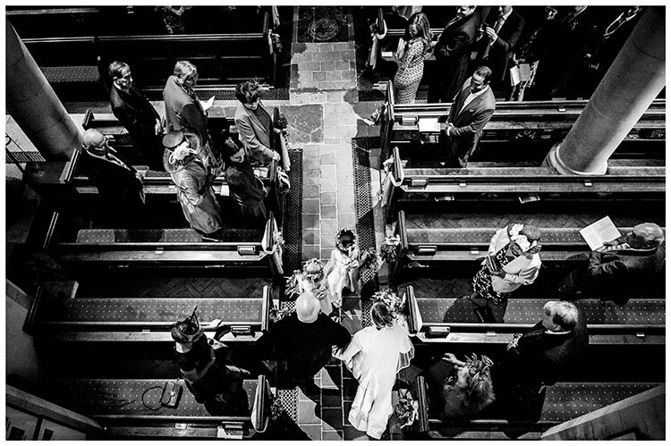 guests watch Bride enter church on arm of father behind flowegirls viewed from above